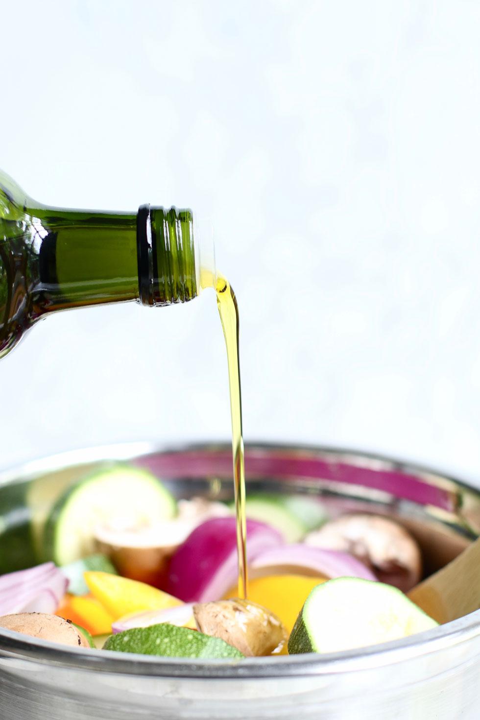 Pouring olive oil on vegetables