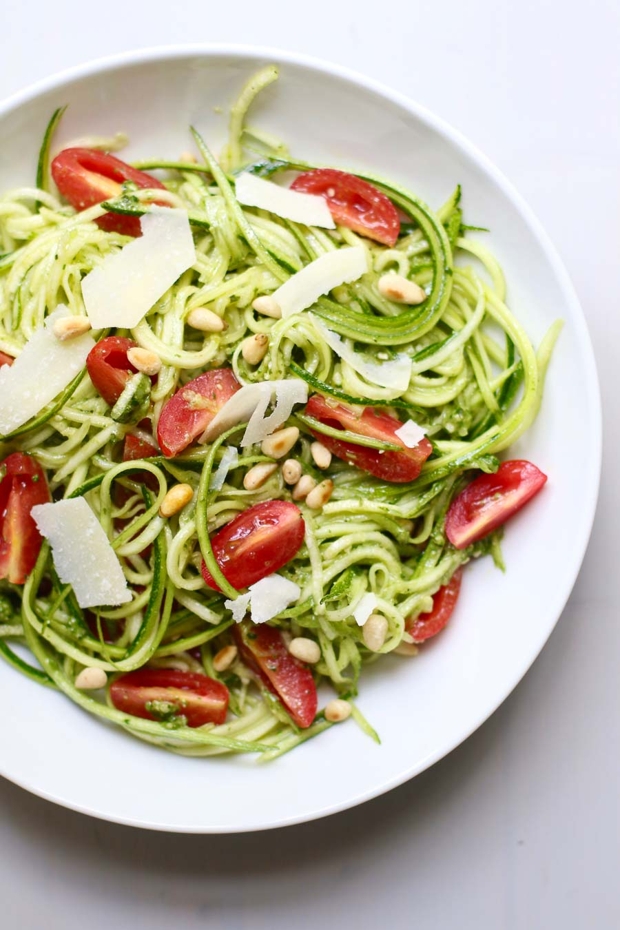 Pesto Zucchini Noodle Salad topped with pine nuts and shaved parmesan
