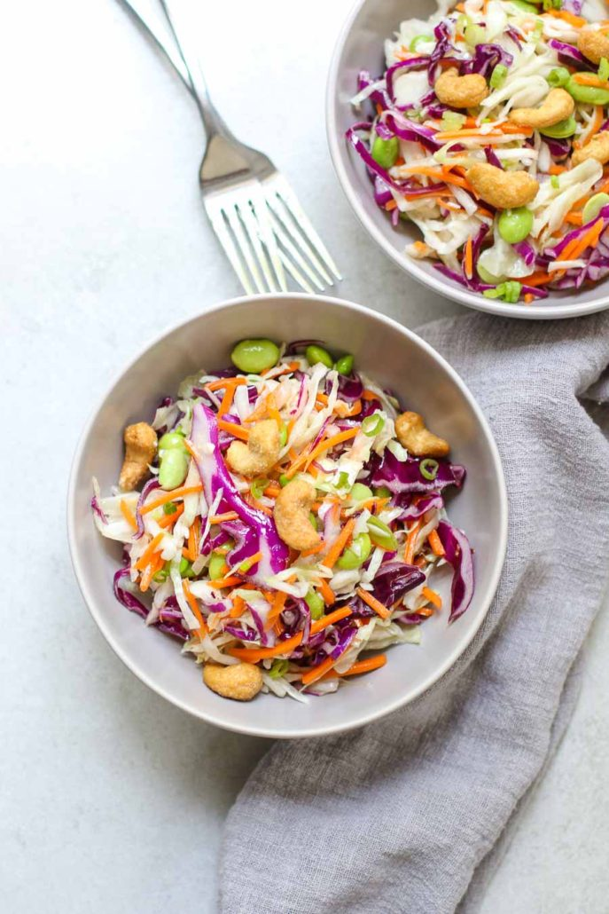 Cashew Cabbage Salad in two serving bowls with two forks and a gray napkin