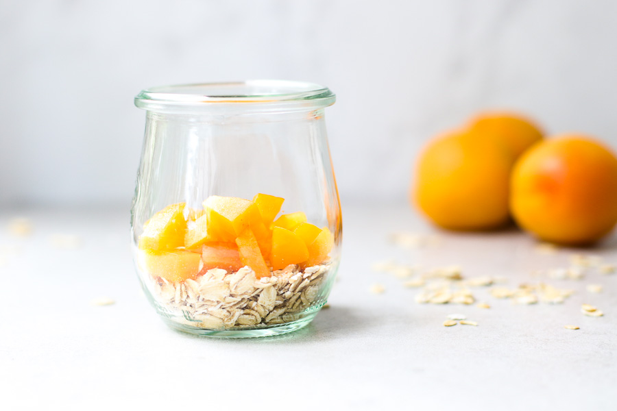 Oats topped with apricots in a jar with apricots in the background