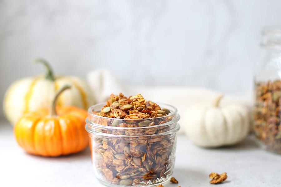 Pumpkin spice granola in a jar with mini pumpkins