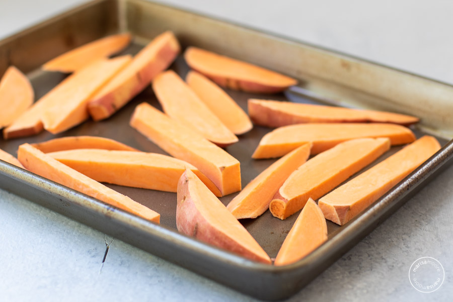 sliced sweet potato wedges on a sheet pan