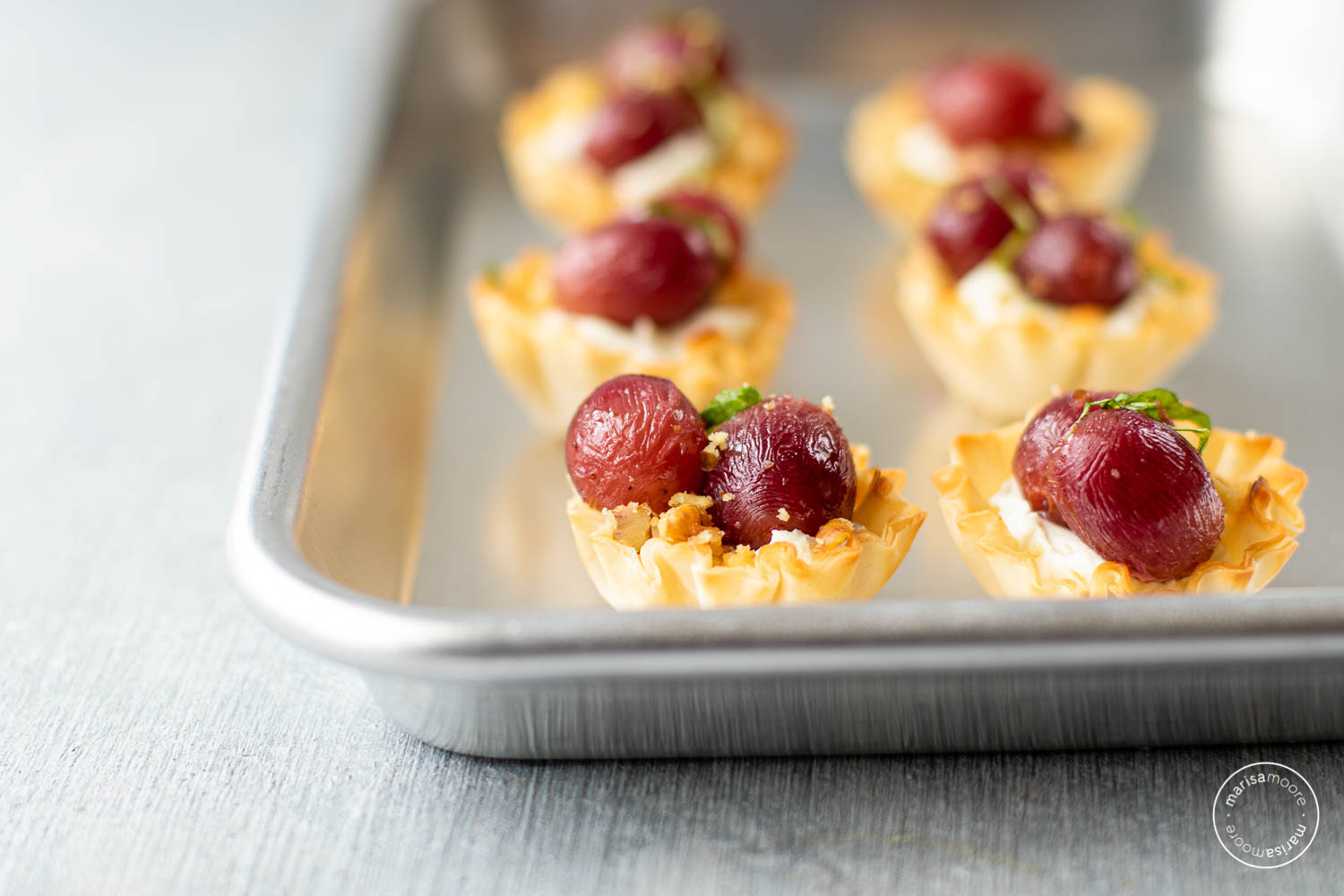 grape and ricotta walnut bites on a sheet tray