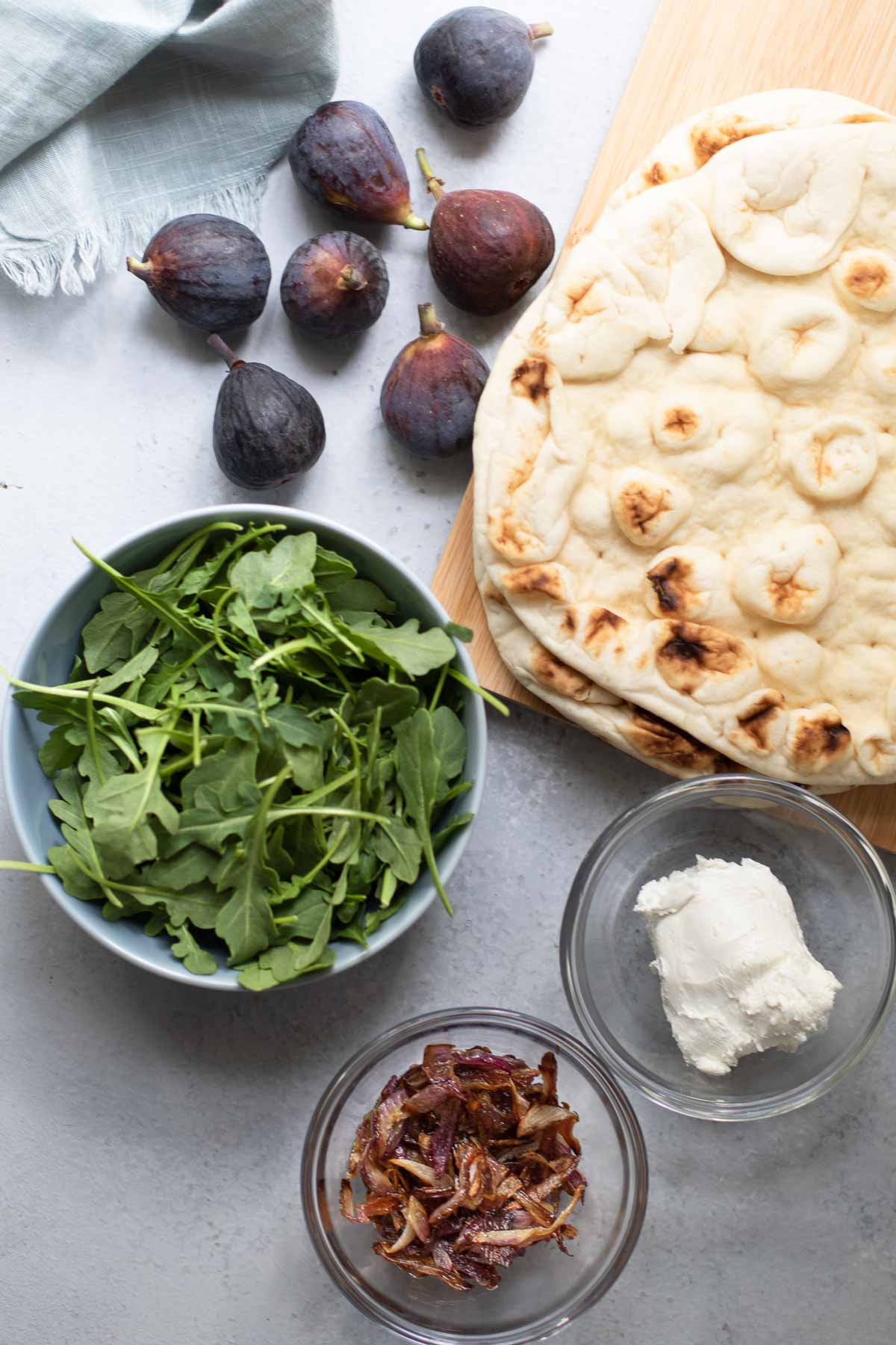 Figs, arugula in a blue bowl, caramelized onions and goat cheese in clear bowls, naan on a cutting board.