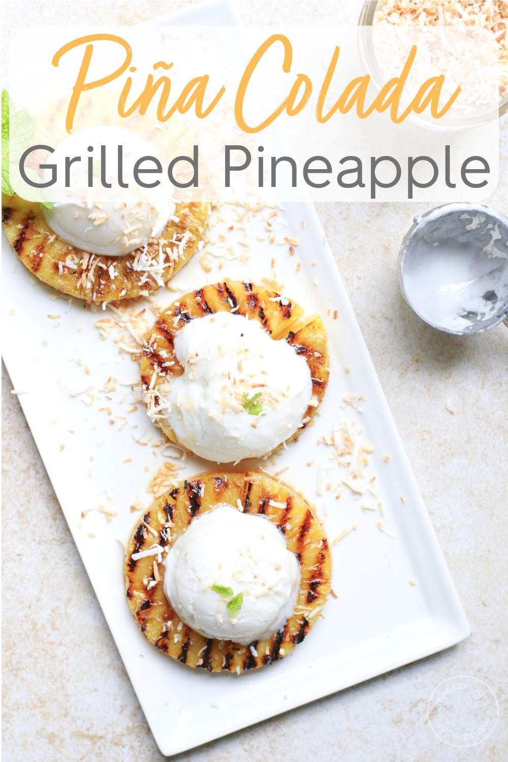 Grilled pineapple topped with coconut ice cream and toasted coconut on a plate