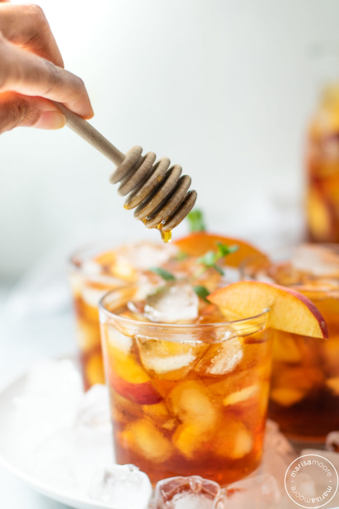 Iced Tea with peaches and a drizzle of honey above
