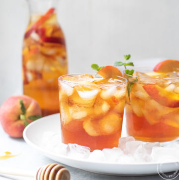 Iced Tea with peaches with a honey spoodle in front
