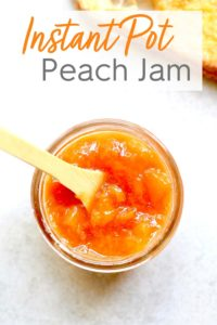 Peach Jam in a jar with a small wooden spoon dipper