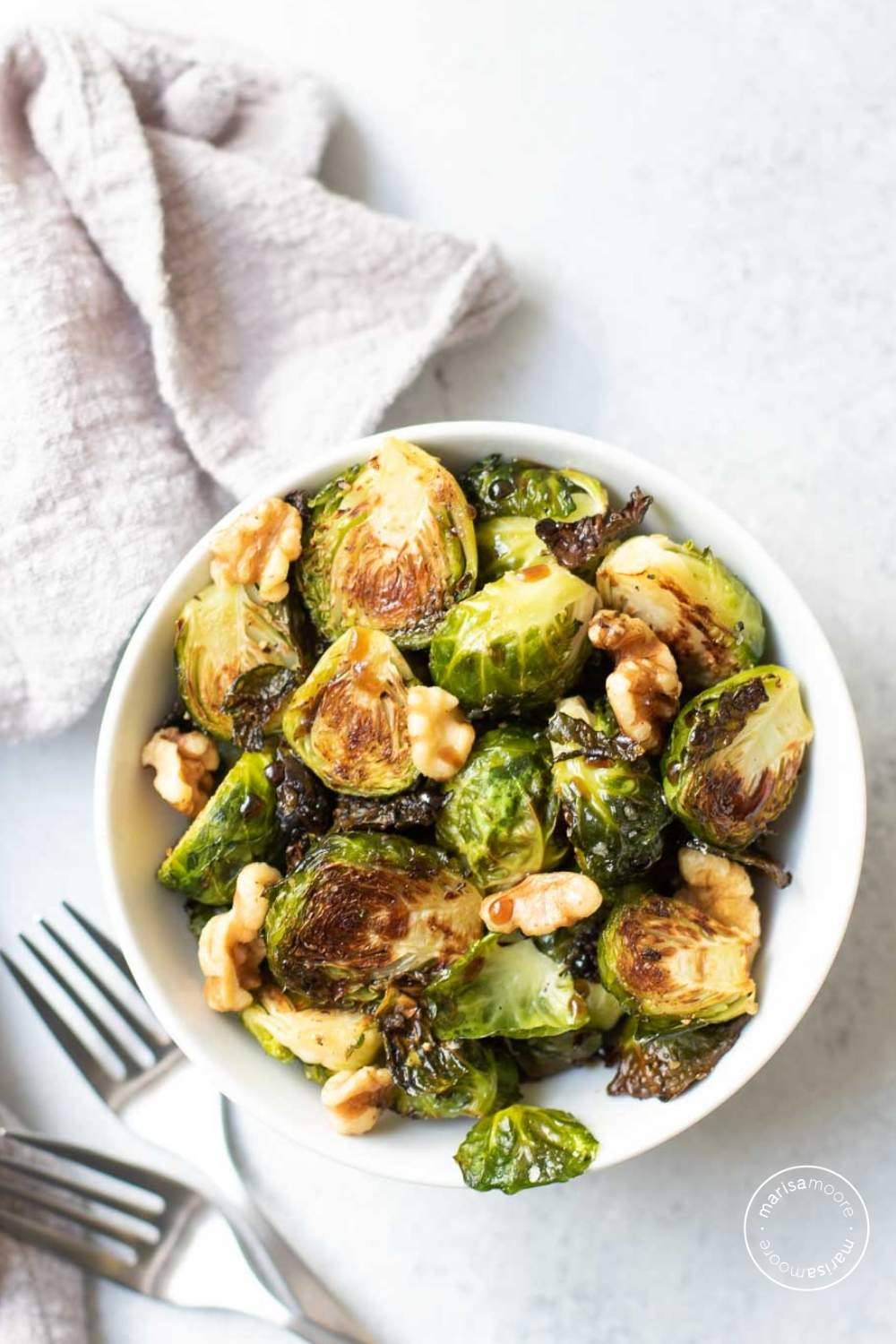 Roasted Brussels Sprouts in a white bowl with a gray napkin and two forks