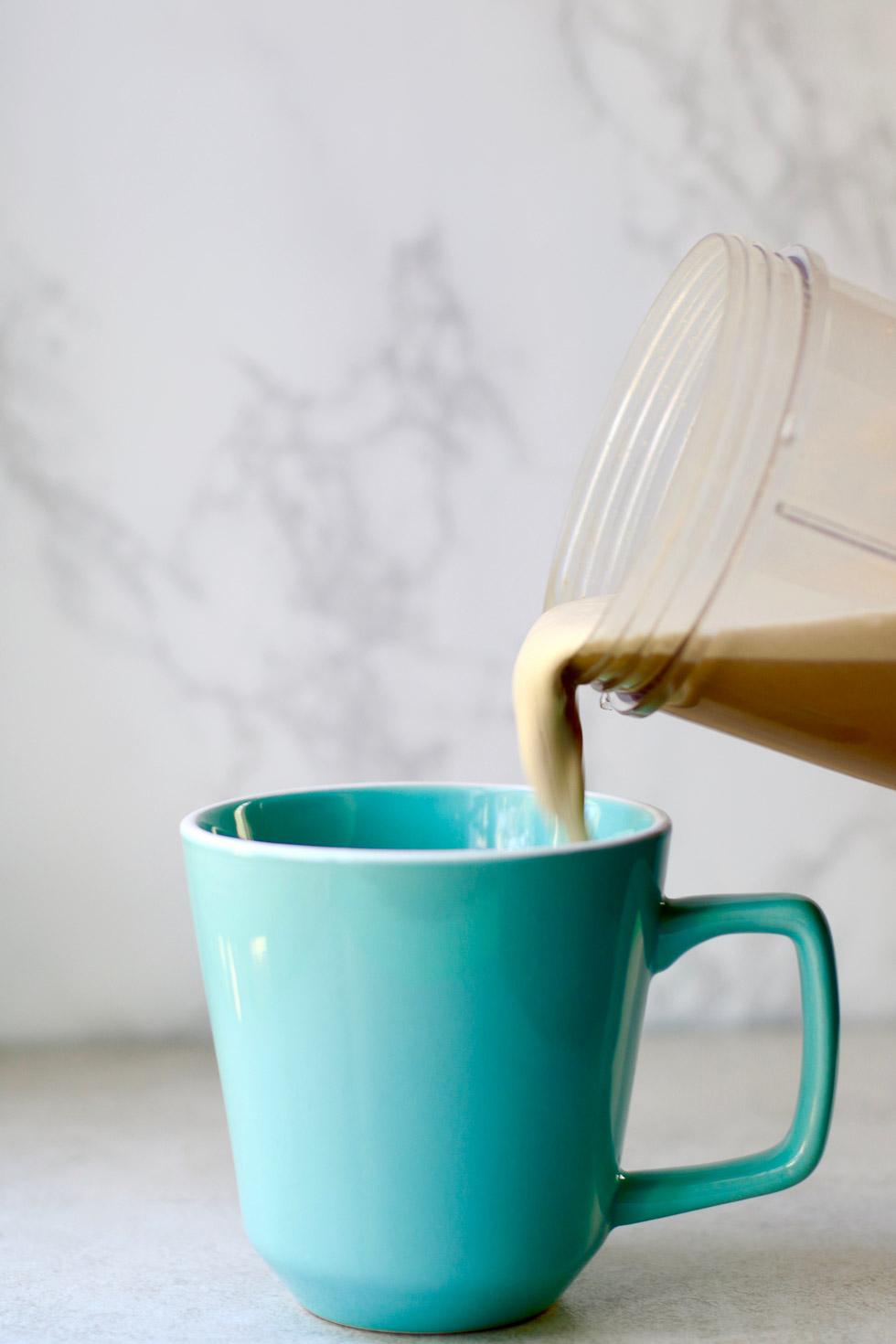pouring cashew coffee into a blue mug