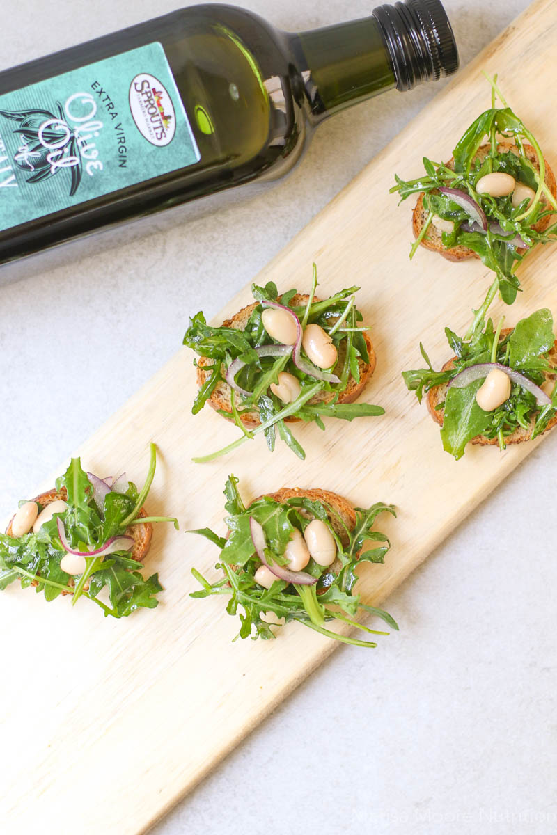Overhead White Bean Arugula Crostini with Sprouts brand Italian Olive Oil on side