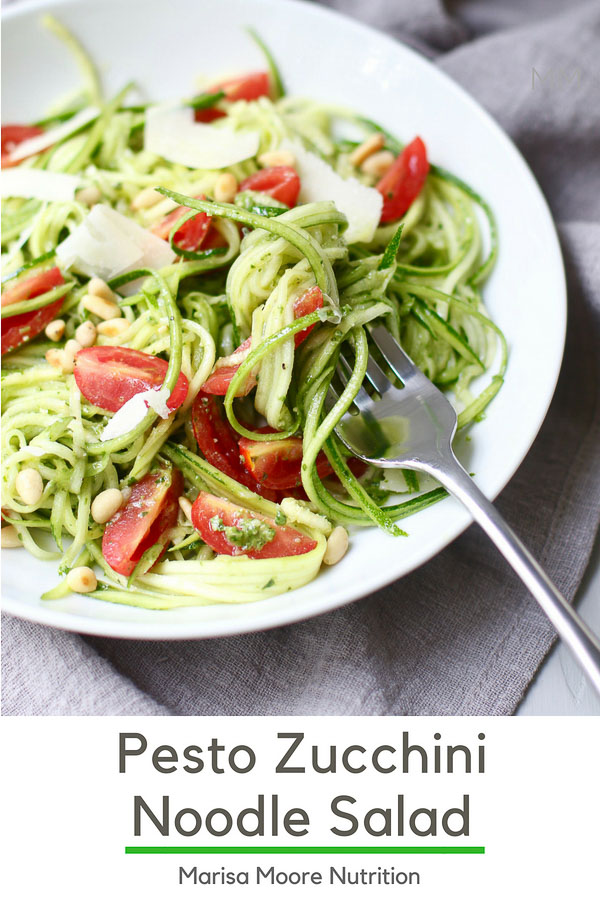 This no-cook Pesto Zucchini Noodle Salad is topped with parmesan, pine nuts, and fresh tomatoes. Use up your summer garden vegetables in this easy salad that's ready in 10 minutes! #pesto #zucchininoodles #nocookmeals #zoodles #summervegetables #marisamoorenutrition