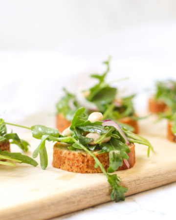 White Bean Arugula Crostini on slim wooden cutting board