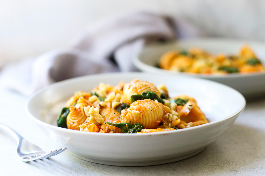 Front view Pumpkin Pasta with Spinach in bowls with fork