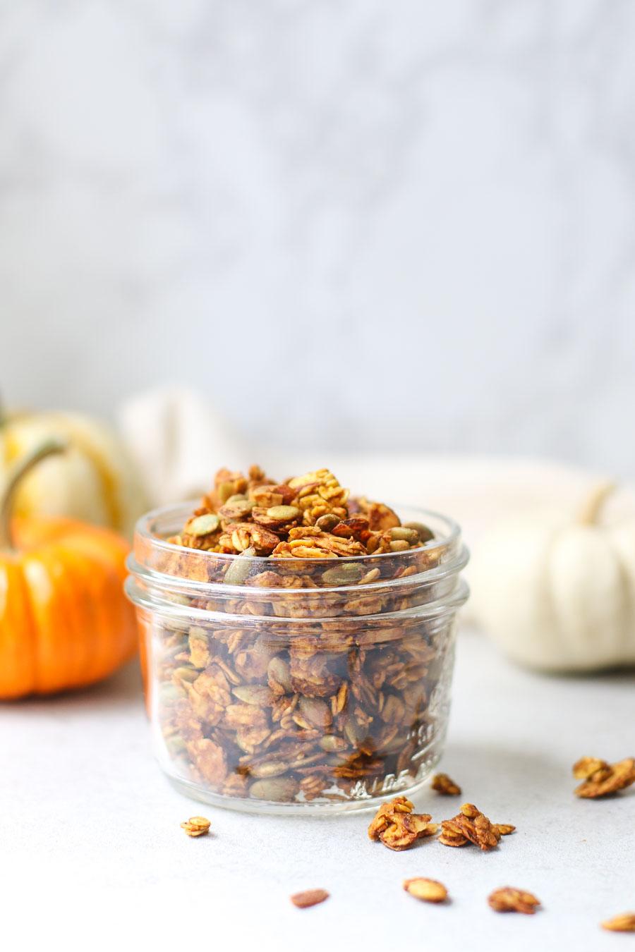 Pumpkin spice granola in small mason jar with mini colored pumpkins in the background