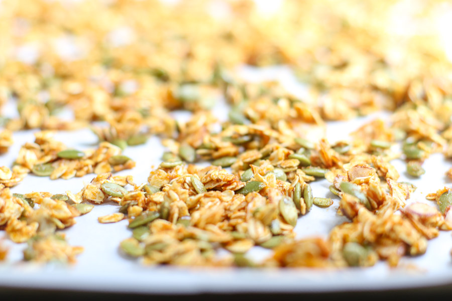 Pumpkin spice granola on parchment before baking