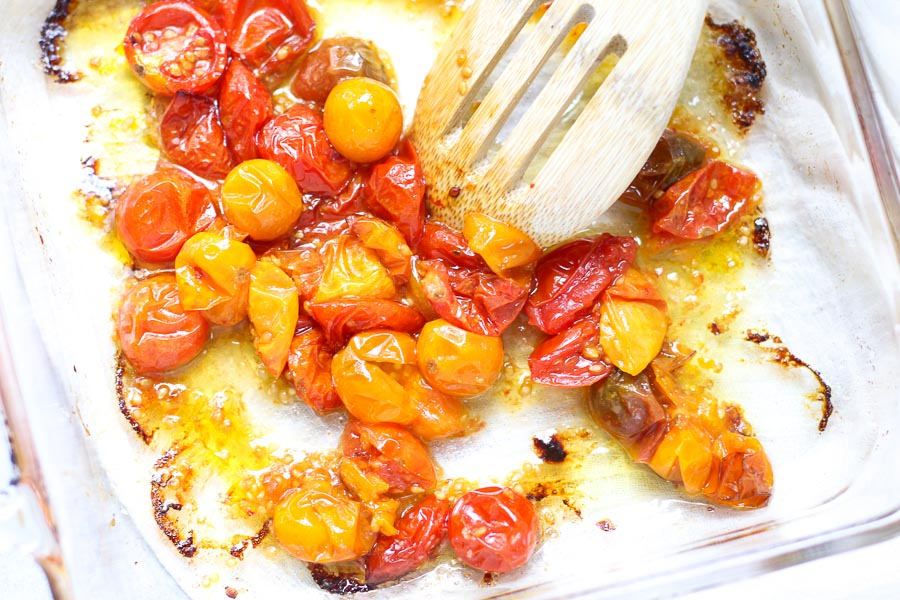 Cooked multi color cherry tomatoes in a glass baking dish