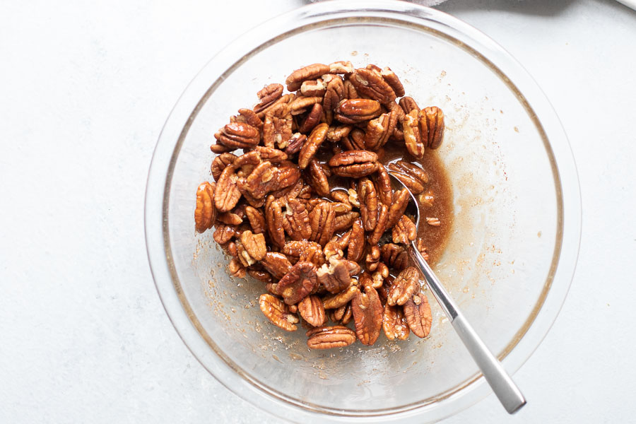 stirring glaze onto pecans in a bowl