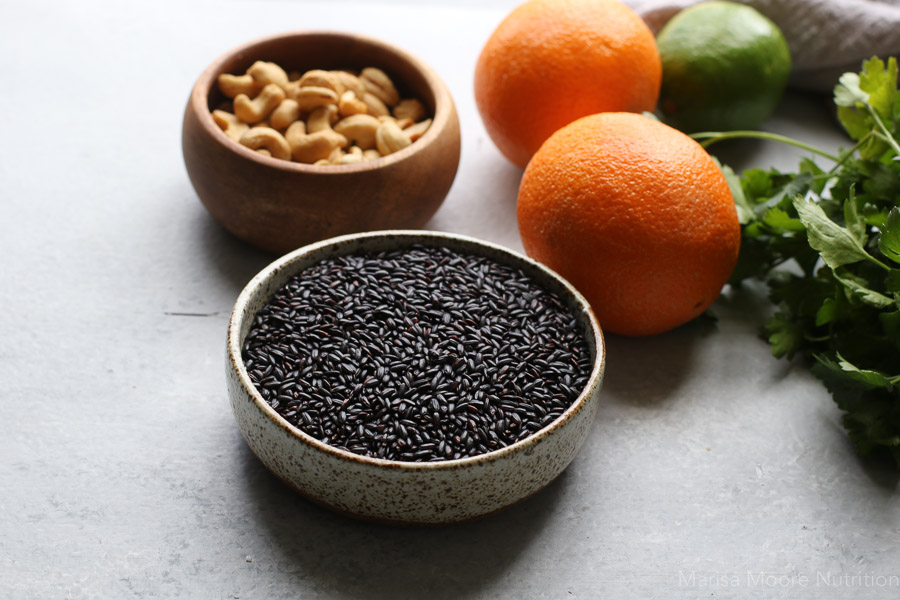 black rice and cashews in bowls with whole oranges in the background