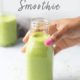Green smoothie with hemp seeds and a hand grabbing the bottle