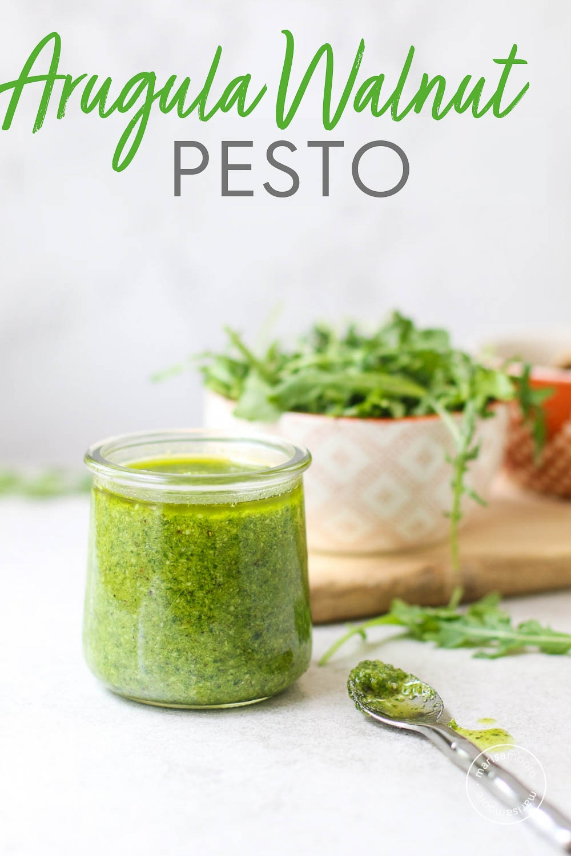 Arugula Walnut Pesto in a small jar with arugula in background