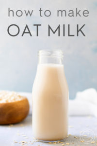 oat milk in a bottle with dry oats scattered around