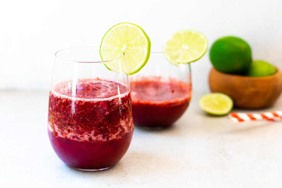 Cherry Lime Slushies in a glass with slice of lime