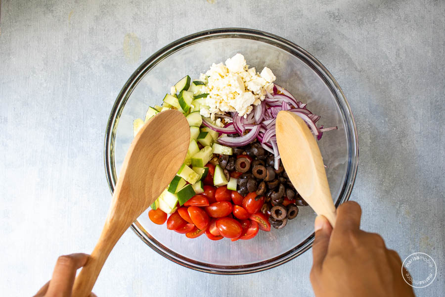 Making Mediterranean Pasta Salad in Bowl with two spoons