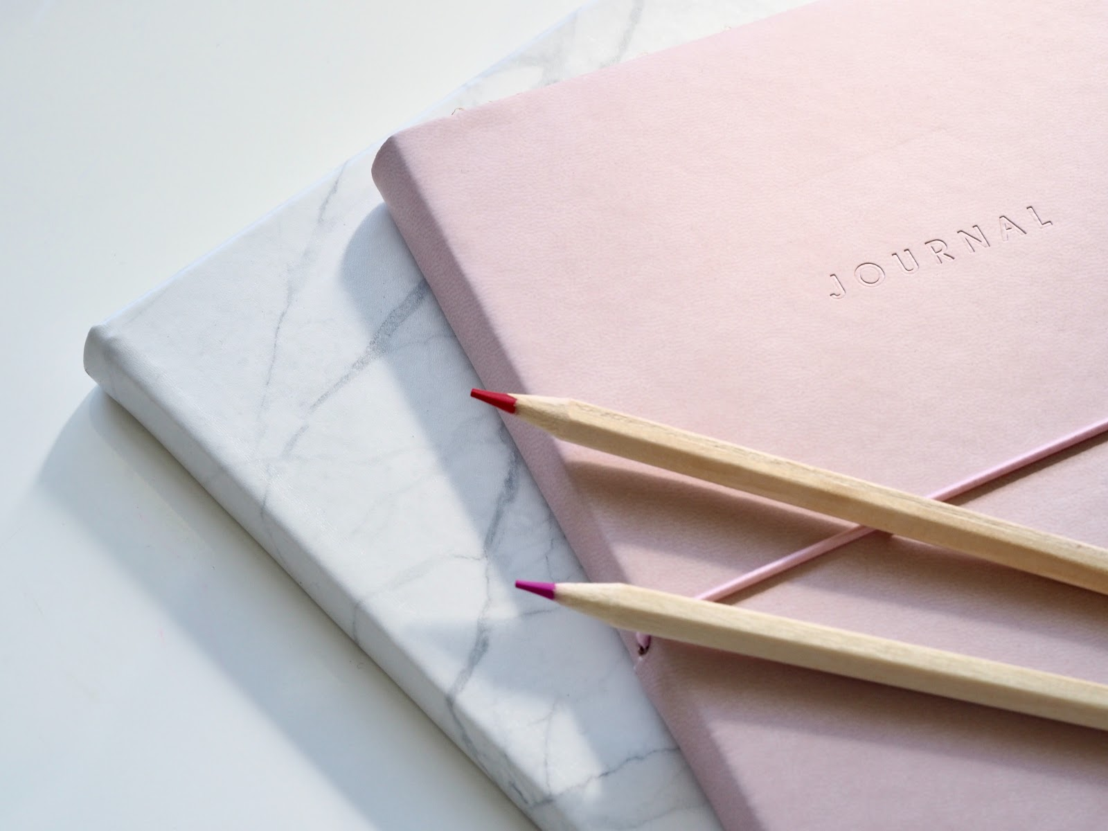 pink journal with 2 pencils