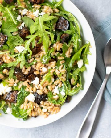 Fig Farro Arugula Salad in white bowl with blue napkin and utensils