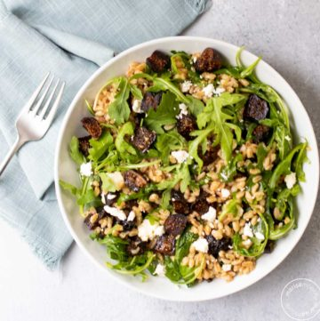 California Fig Farro Salad in a bowl with a fork and napkin