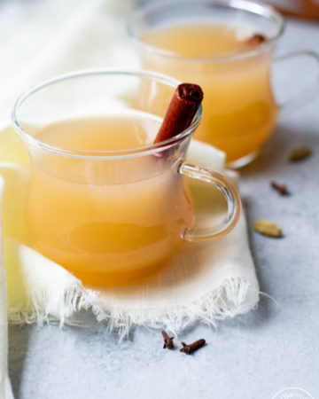 Pear Cider in clear mugs with cinnamon sticks