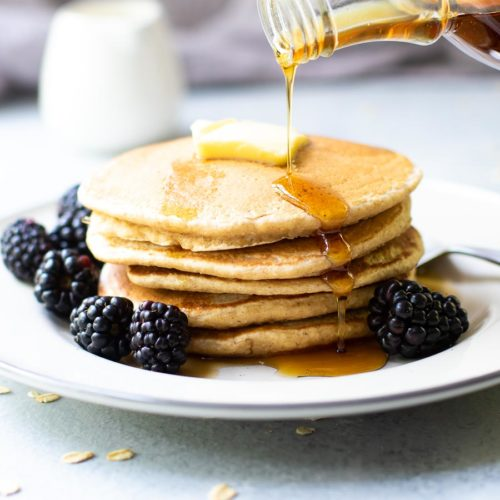 Oat Flour Pancakes with Syrup pouring and blackberries