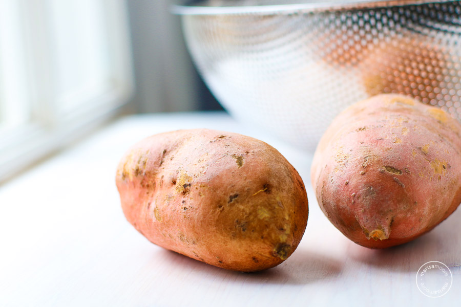 Whole sweet potatoes next to a colander