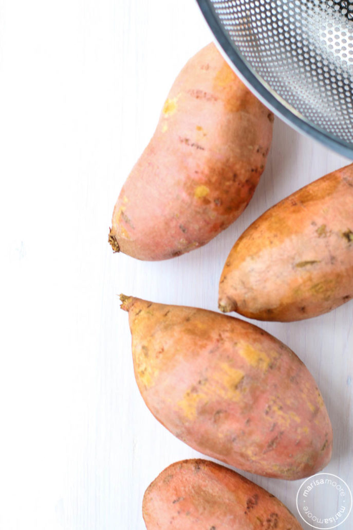Whole sweet potatoes on a white background with colander