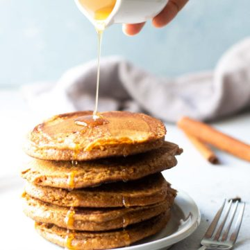 stacked gingerbread pancakes with syrup being poured