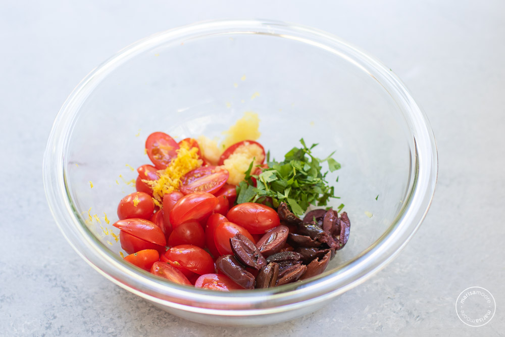 clear mixing bowl filled with tomatoes, garlic, parsley and lemon zest