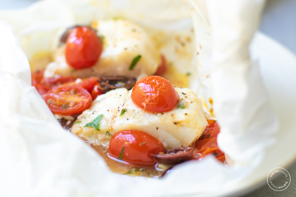fish in parchment with tomatoes on a plate