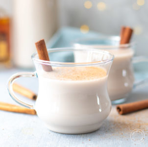 clear glass mug of vegan eggnog with spices on top
