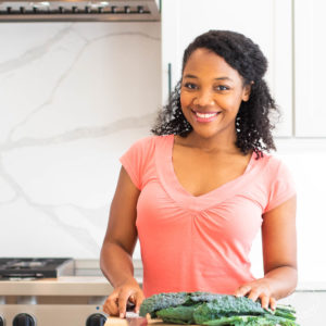 Marisa Moore in a white kitchen with greens on a cutting board