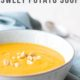 sweet potato soup in a grey bowl with blue napkin