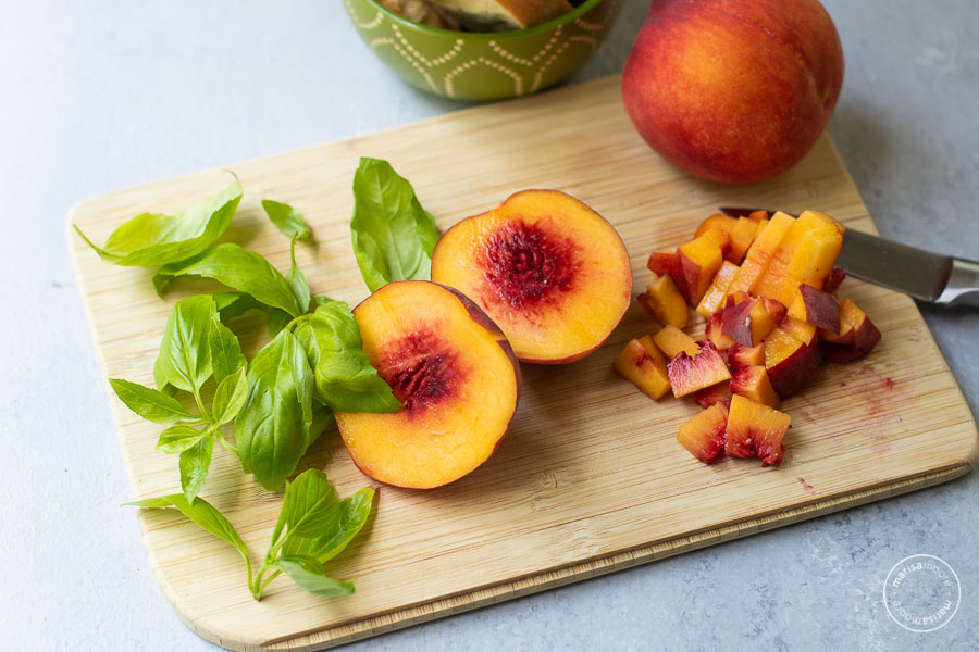fresh basil leaves and chopped peaches on a cutting board