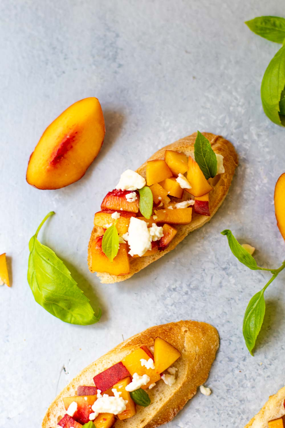 Peach toasts on a light background with fresh basil leaves scattered