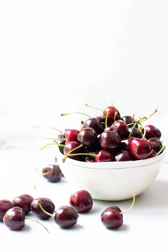 cherries in a white bowl and scattered around the bowl