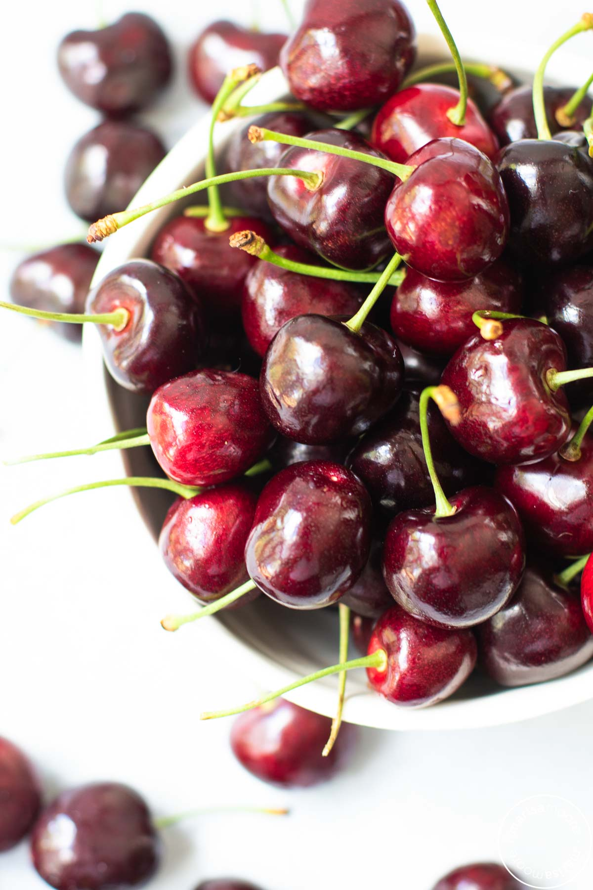 fresh dark sweet cherries with green stems in a white bowl with cherries scattered around
