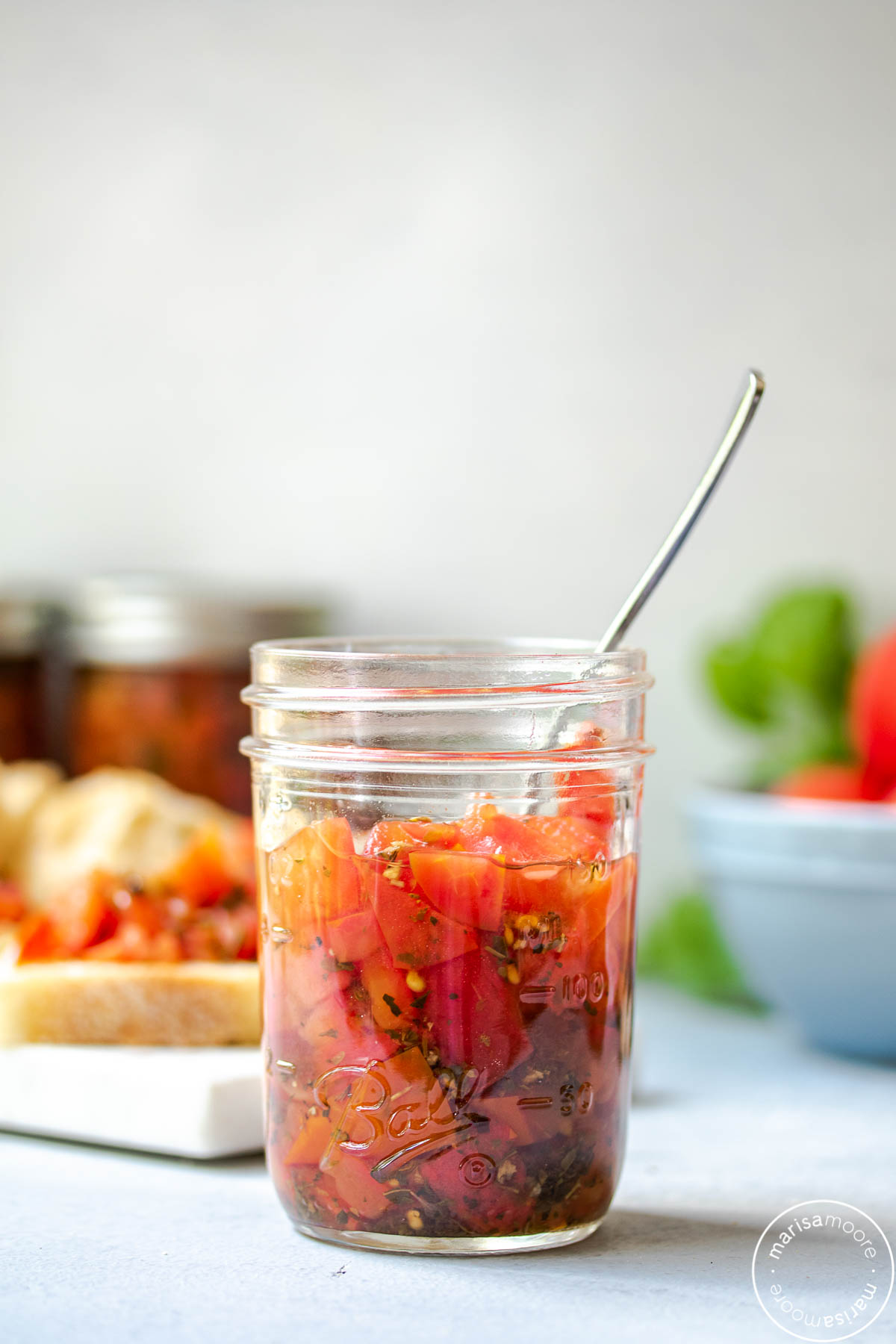half pint jar of bruschetta with crostinis in the background