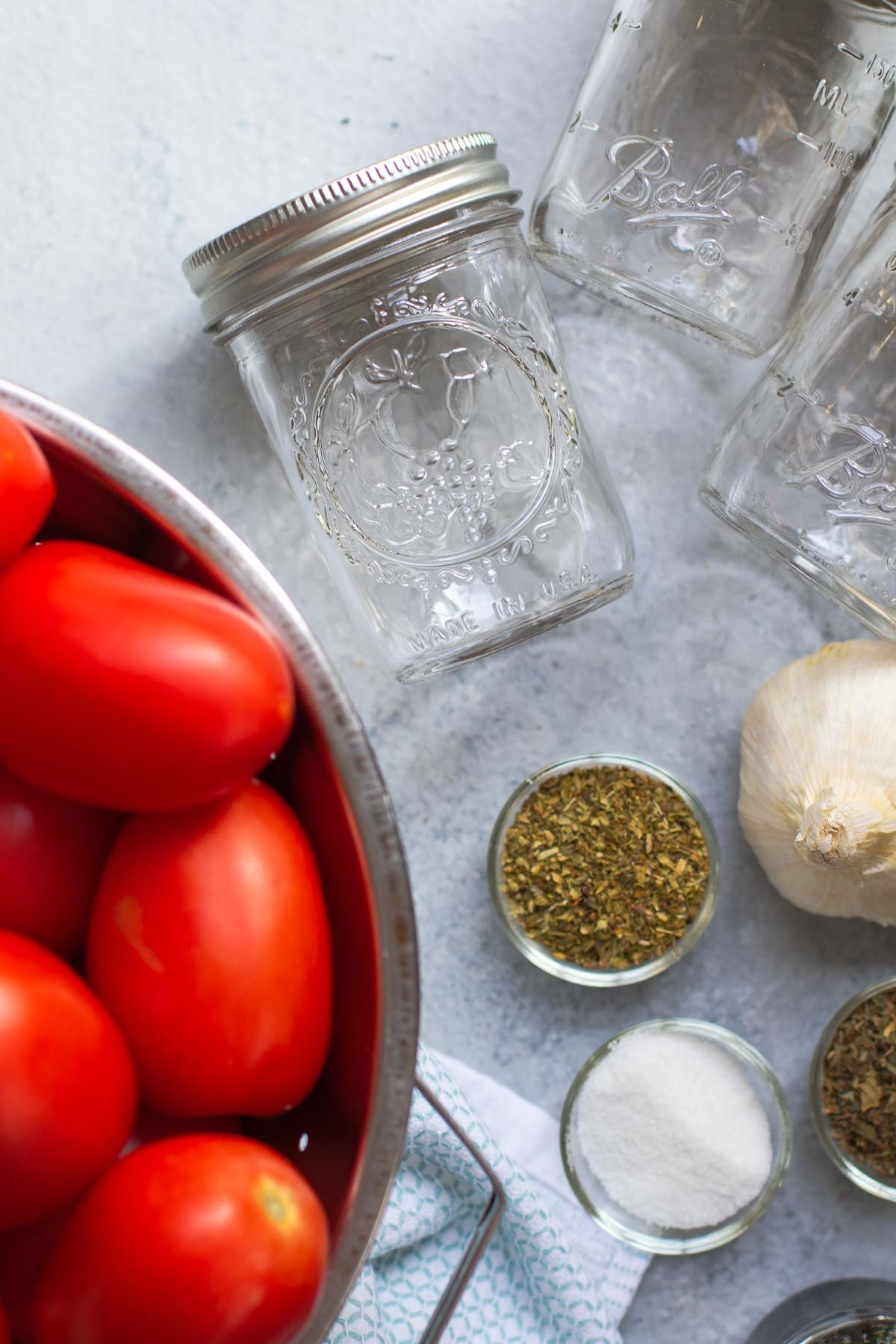 Ingredients in a flatlay - tomatoes, herbs, sugar and half pint jars