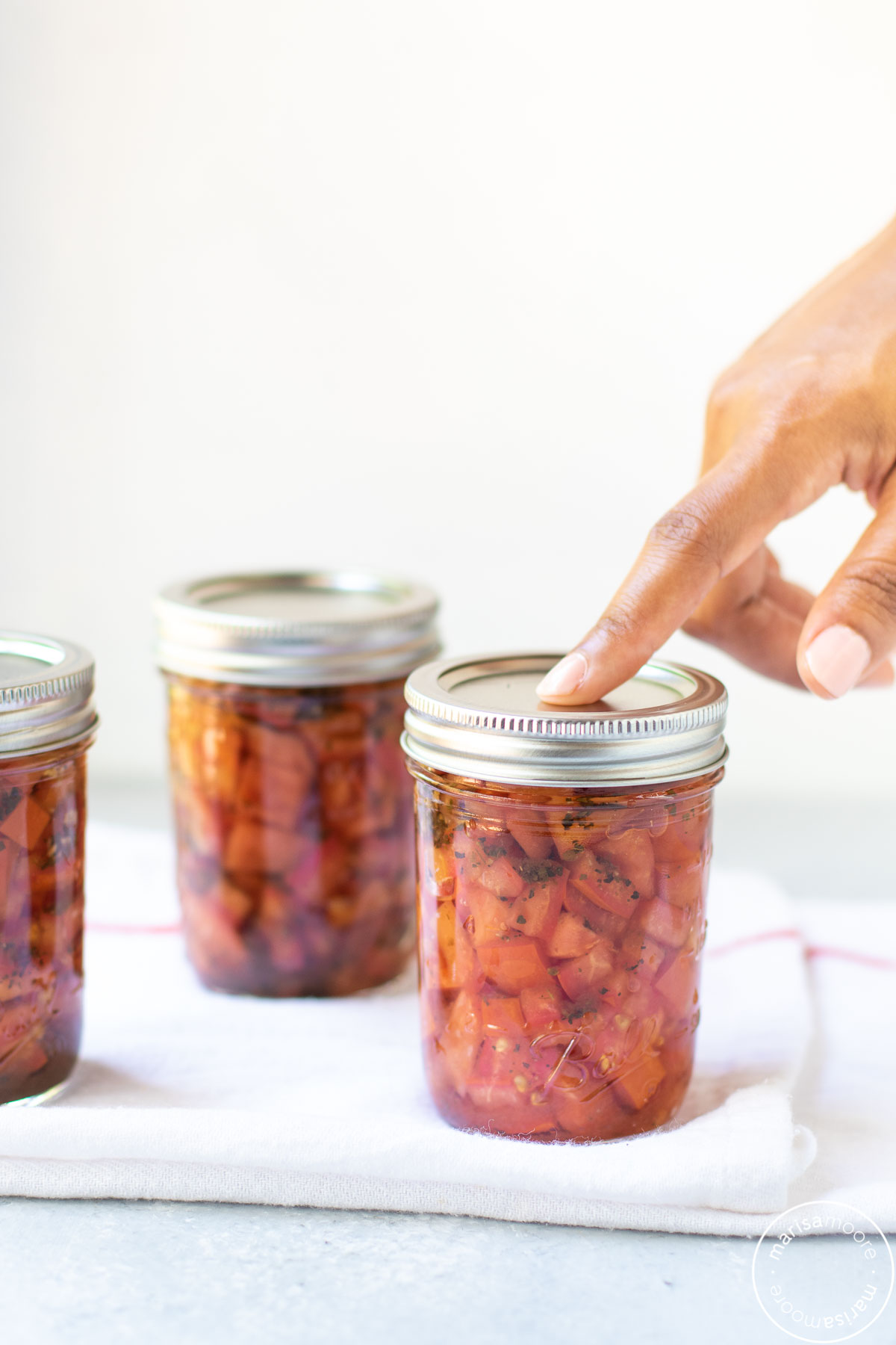 pressing the top of a jar with an index finger