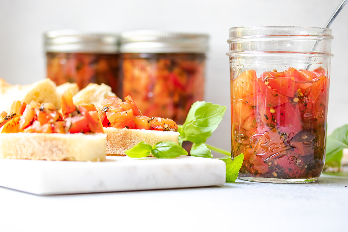 Bruschetta tomatoes in a jar with a snack board and pieces of crostini topped with marinated tomatoes and basil