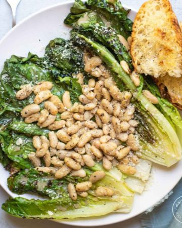 Grilled romaine topped with white beans and grilled bread on white plate